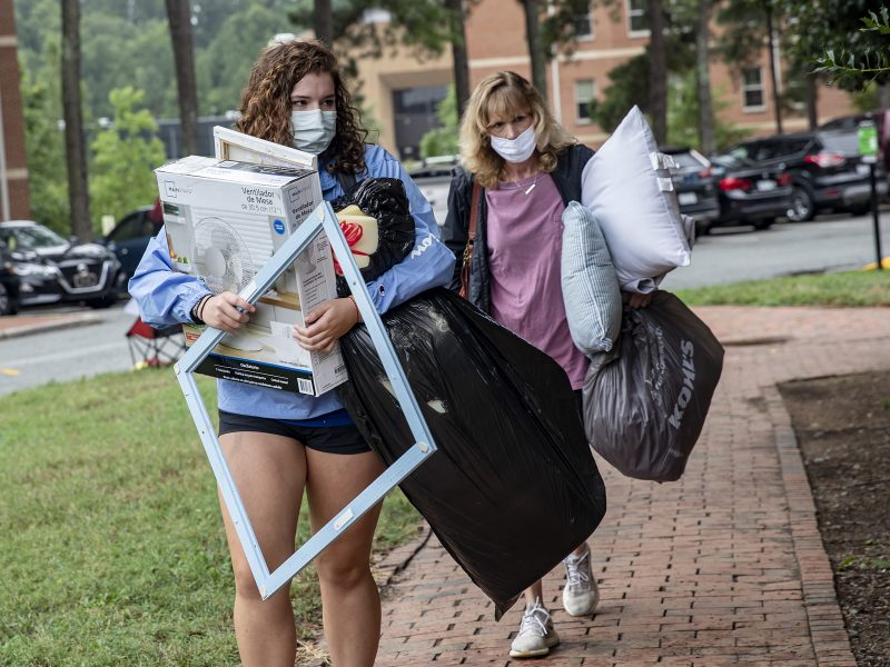 two woman wearing masks, carrying belongings toward a residence hall