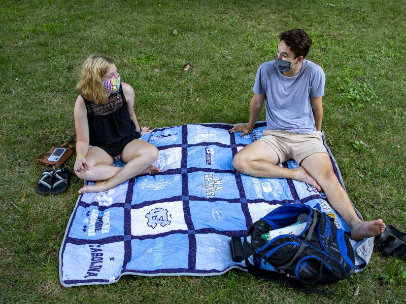 Two students wearing a mask while having a picnic and sitting a part.